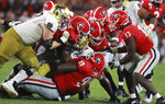 The Georgia defense led by defensive lineman Jordan Davis, bottom, who arrived first, smothers Notre Dame running back Tony Jones Jr. during the third quarter of an NCAA college football game Saturday, Sept. 21, 2019, in Athens, Ga. (Curtis Compton/Atlanta Journal Constitution via AP)