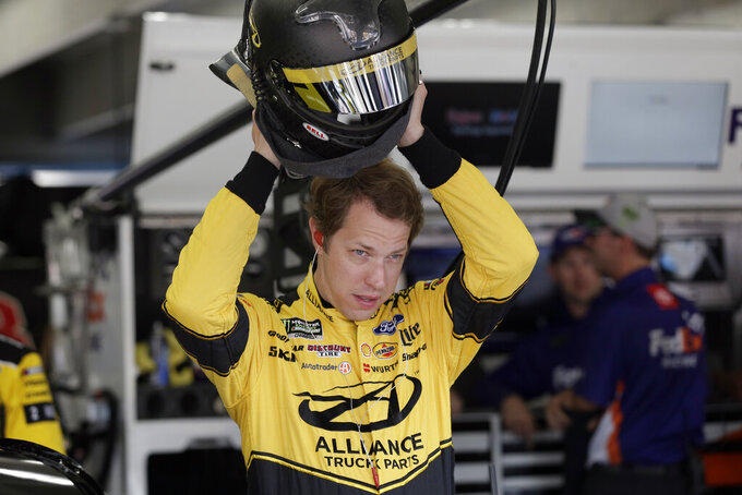 Brad Keselowski puts on his helmet during practice for Sunday's NASCAR Cup Series auto race at Charlotte Motor Speedway in Concord, N.C., Saturday, Sept. 28, 2019. (AP Photo/Gerry Broome)