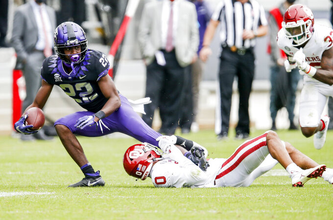 Oklahoma safety Woodi Washington (0) tackles TCU wide receiver Blair Conwright (22) during the second half of an NCAA college football game, Saturday, Oct. 24, 2020, in Fort Worth, Texas.  (AP Photo/Brandon Wade)