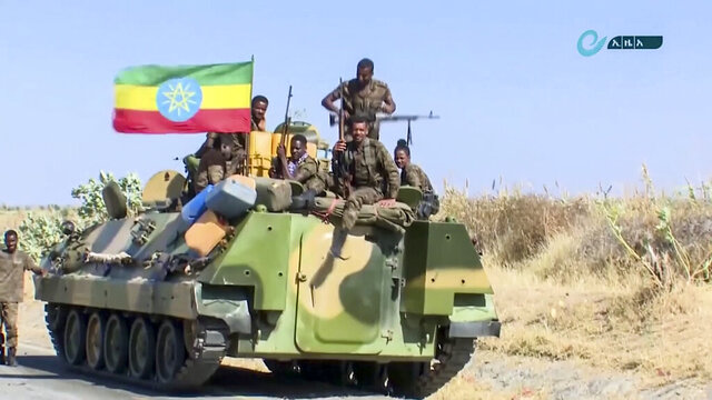 This image made from undated video released by the state-owned Ethiopian News Agency on Monday, Nov. 16, 2020 shows Ethiopian military sitting on an armored personnel carrier next to a national flag, on a road in an area near the border of the Tigray and Amhara regions of Ethiopia. Ethiopia's prime minister Abiy Ahmed said in a social media post on Tuesday, Nov. 17, 2020 that