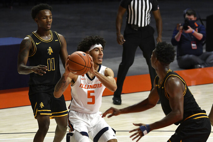 Illinois' Andre Curbelo (5) looks to pass as he is pressured by North Carolina A&T's Tyler Maye (11) and Webster Filmore (25) in the first half  of an NCAA college basketball game Wednesday, Nov. 25, 2020, in Champaign, Ill. (Photo/Holly Hart)