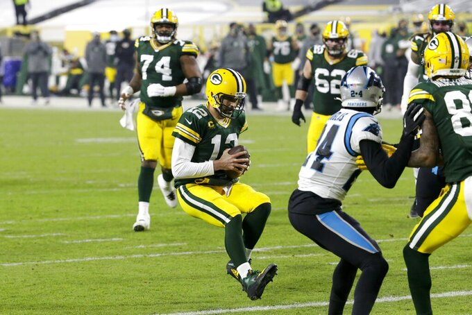 Green Bay Packers' Aaron Rodgers runs for a touchdown during the first half of an NFL football game against the Carolina Panthers Saturday, Dec. 19, 2020, in Green Bay, Wis. (AP Photo/Mike Roemer)