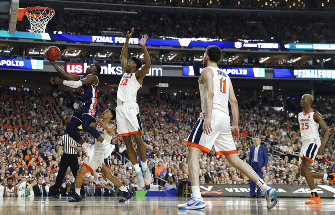 Auburn guard Jared Harper, left, drives to the basket ahead of Virginia defenders during the first half in the semifinals of the Final Four NCAA college basketball tournament, Saturday, April 6, 2019, in Minneapolis. (AP Photo/David J. Phillip)