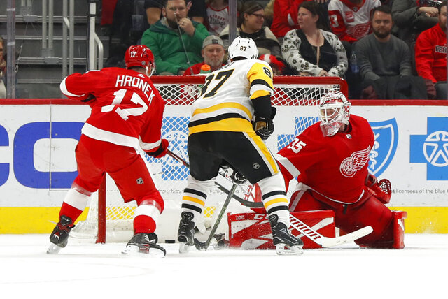 Pittsburgh Penguins center Sidney Crosby (87) scores the winning goal against Detroit Red Wings goaltender Jimmy Howard (35) as Filip Hronek (17) defends as in overtime of an NHL hockey game Friday, Jan. 17, 2020, in Detroit. (AP Photo/Paul Sancya)