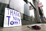 A bouquet of flowers and a sign thanking former New England Patriots quarterback Tom Brady, who announced he was leaving the football team, rest on the sidewalk outside the TB12 training center in Boston, Tuesday, March 17, 2020. (AP Photo/Charles Krupa)