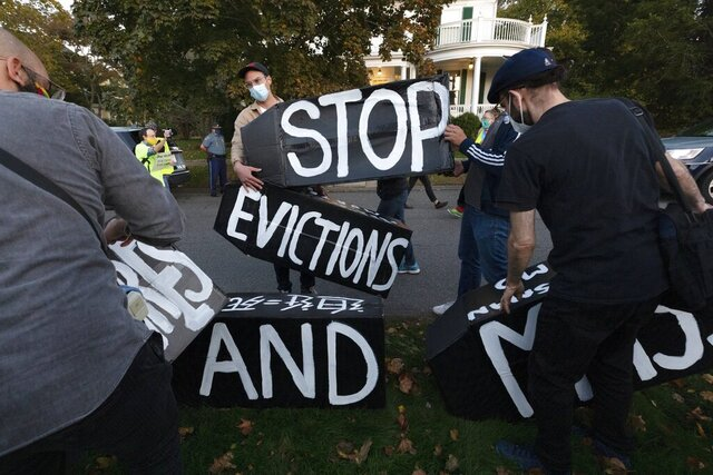 Housing activists erect a sign in front of Massachusetts Gov. Charlie Baker's house, Wednesday, Oct. 14, 2020, in Swampscott, Mass. The protesters were calling on the governor to support more robust protections against evictions and foreclosures during the ongoing coronavirus pandemic. (AP Photo/Michael Dwyer)