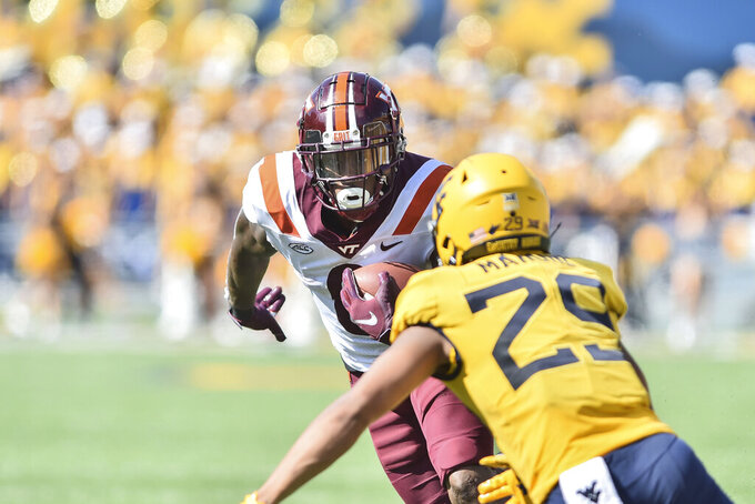 Virginia Tech running back Jalen Holston (0) slips a tackle by West Virginia safety Sean Mahone (29) during the second half of  an NCAA college football game in Morgantown, W.Va., Saturday, Sep. 18, 2021. (AP Photo/William Wotring)