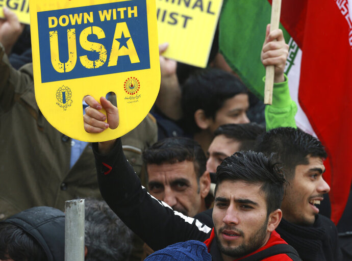 A demonstrator holds an anti-U.S. placard during a ceremony celebrating the 40th anniversary of the Islamic Revolution, at the Azadi, Freedom, Square in Tehran, Iran, Monday, Feb. 11, 2019. Crowds streamed in the rain from a dozen of the capital's far-flung neighborhoods to mass in central Tehran, waving Iranian flags and chanting