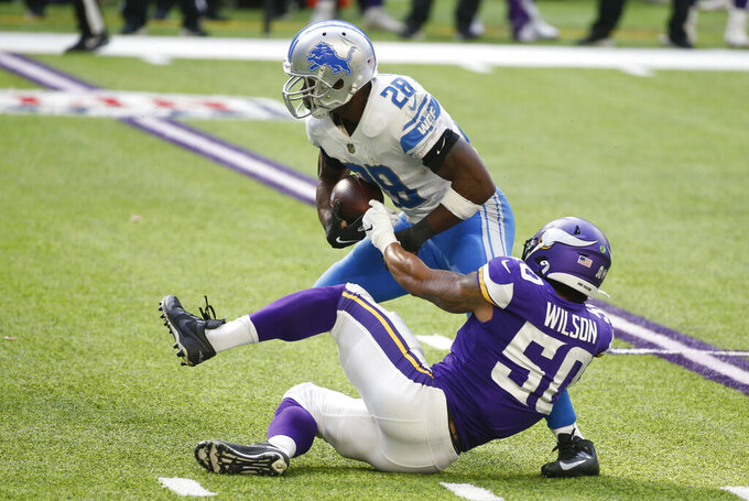 Detroit Lions running back Adrian Peterson (28) is tackled by Minnesota Vikings linebacker Eric Wilson (50) during the first half of an NFL football game, Sunday, Nov. 8, 2020, in Minneapolis. (AP Photo/Bruce Kluckhohn)