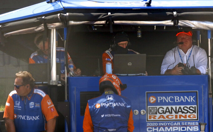Car owner Chip Ganassi, right, sits in the pit box on pit road during an IndyCar race at Mid-Ohio Sports Car Course in Lexington, Ohio, Sunday, July 4, 2021. (AP Photo/Tom E. Puskar)