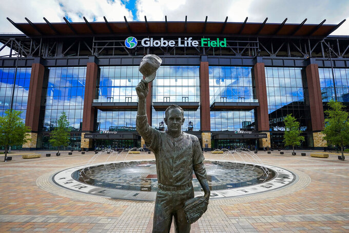 FILE - In this March 31, 2020, file photo, a statue of Nolan Ryan stands in the empty plaza outside Globe Life Field in Arlington, Texas. The new Texas Rangers ballpark is among possible venues Major League Baseball could use if it decides to start the season with groups of teams in different areas. Among the different plans looked at by Major League Baseball is to use Texas as a mid-American hub. (Smiley N. Pool/The Dallas Morning News via AP, Pool, File)
