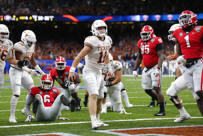 Texas quarterback Sam Ehlinger (11) reacts after scoring a touchdown, between Georgia linebacker Natrez Patrick (6), defensive lineman Devonte Wyatt (95) and linebacker Brenton Cox (1) during the first half of the Sugar Bowl NCAA college football game in New Orleans, Tuesday, Jan. 1, 2019. (AP Photo/Gerald Herbert)