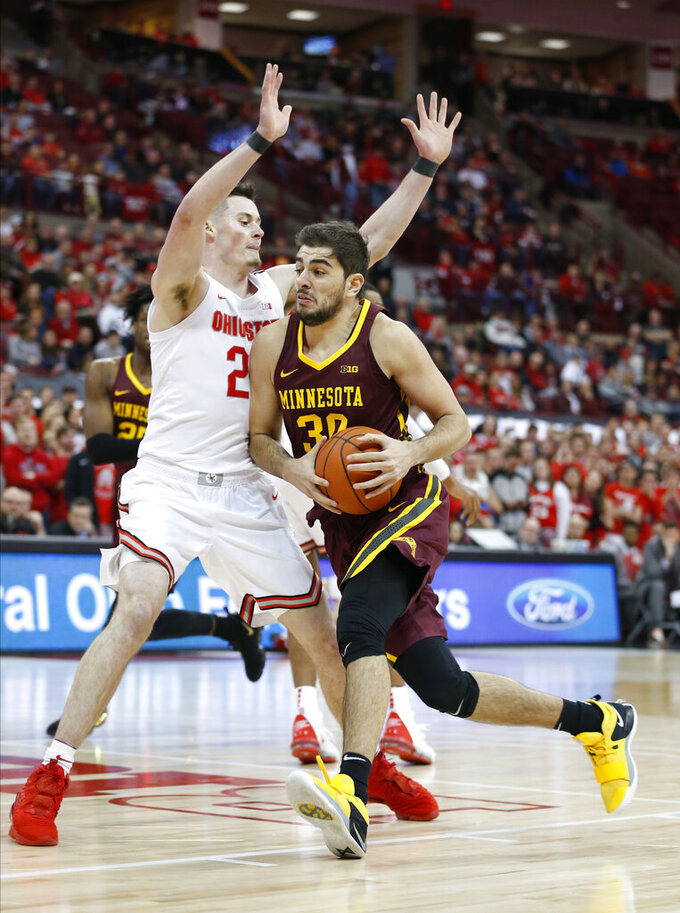 Minnesota's Alihan Demir, right, drives the lane against Ohio State's Kyle Young during the first half of an NCAA college basketball game Thursday, Jan. 23, 2020, in Columbus, Ohio. (AP Photo/Jay LaPrete)