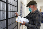 In this Wednesday, May 6, 2020 photo, Vaino Kola picks up his mail at the post office on Deer Isle, Maine. From coastal Maine to Philadelphia's close-knit neighborhoods, many residents call the postal service essential to their communities. (AP Photo/Robert F. Bukaty)