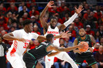 North Texas' Umoja Gibson (1) attempts a pass against Dayton's Jordy Tshimanga (32) and Jalen Crutcher, above, during the first half of an NCAA college basketball game, Tuesday, Dec. 17, 2019, in Dayton, Ohio. (AP Photo/John Minchillo)