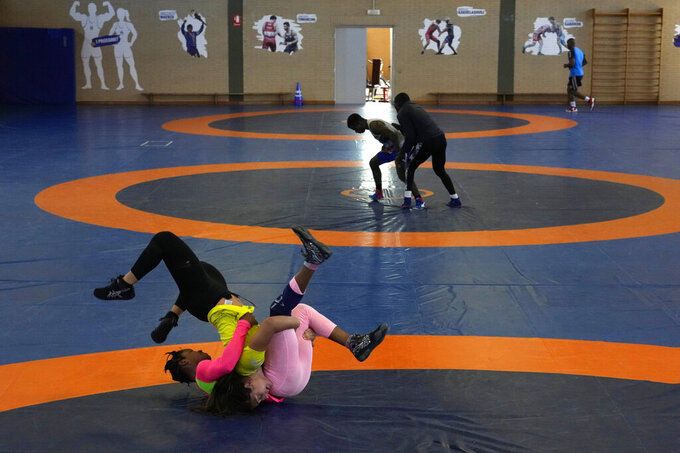 Guinean wrestler Fatoumata Yarie Camara, right, competes with Italian athlete Morena De Vita during her morning training session at the Ostia's Olympic training center, near Rome, Monday, July 5, 2021. A West African wrestler's dream of competing in the Olympics has come down to a plane ticket. Fatoumata Yarie Camara is the only Guinean athlete to qualify for these Games. She was ready for Tokyo, but confusion over travel reigned for weeks. The 25-year-old and her family can't afford it. Guinean officials promised a ticket, but at the last minute announced a withdrawal from the Olympics over COVID-19 concerns. Under international pressure, Guinea reversed its decision.  (AP Photo/Alessandra Tarantino)