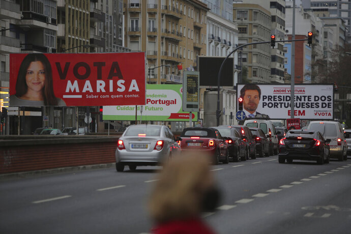 Cars drive past election campaign billboards for presidential candidates Marisa Matias, left, and Andre Ventura, right, in Lisbon, Tuesday, Jan. 19, 2021. Portugal holds a presidential election on Sunday, Jan. 24, 2021 and the moderate incumbent candidate is widely seen as the sure winner. But an intriguing question for many Portuguese is how well a brash new populist challenger fares in the ballot. Mainstream populism is a novelty in Portugal. (AP Photo/Armando Franca)
