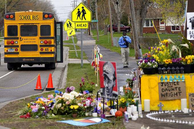 A school bus driver stops to look at a makeshift memorial at the site where Daunte Wright was killed a day after he was laid to rest, Friday, April 23, 2021, in Brooklyn Center, Minn. The 20-year-old Wright was killed by then-Brooklyn Center police officer Kim Potter during a traffic stop. (AP Photo/Julio Cortez)