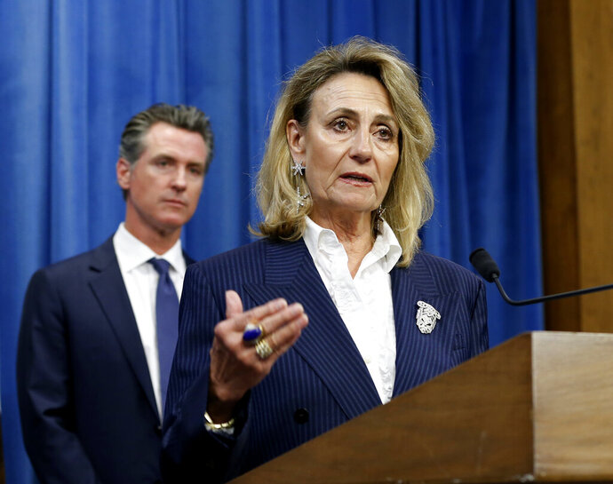 FILE - In this July 23, 2019, file photo, Marybel Batjer, of the California Public Utilities Commission, speaks during a news conference as Gov. Gavin Newsom looks on in Sacramento, Calif. California's utility regulator is issuing a series of sanctions against Pacific Gas and Electric for what it calls