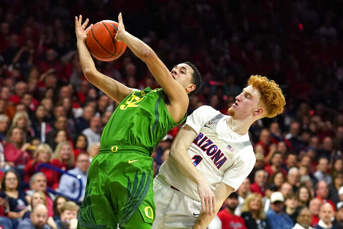 Oregon guard Anthony Mathis (32) is fouled by Arizona guard Nico Mannion during the first half of an NCAA college basketball game Saturday, Feb. 22, 2020, in Tucson, Ariz. (AP Photo/Rick Scuteri)