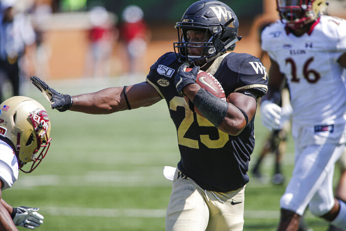 Wake Forest running back Kenneth Walker stiff arms an Elon defender on his way to scoring a touchdown in the second half of an NCAA college football game in Winston-Salem, N.C., Saturday, Sept. 21, 2019. Wake Forest won 49-7. (AP Photo/Nell Redmond)