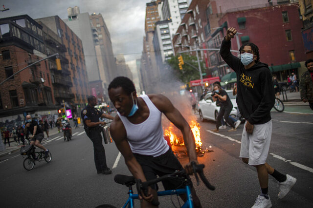 Protesters march down the street as trash burns in the background during a solidarity rally for George Floyd, Saturday, May 30, 2020, in New York. Protests were held throughout the city over the death of George Floyd, a black man who died after being restrained by Minneapolis police officers on May 25. (AP Photo/Wong Maye-E)