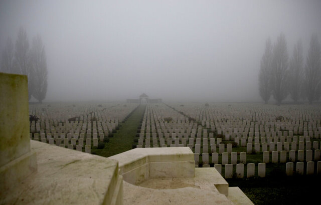 The Tyne Cot cemetery, empty of visitors and shrouded in fog, viewed from the Cross of Sacrifice on Armistice Day in Zonnebeke, Belgium, Wednesday, Nov. 11, 2020. The Tyne Cot Commonwealth War Graves Cemetery and Memorial to the Missing is a burial ground for the dead of the First World War in the Ypres Salient on the Western Front. It is the largest cemetery for Commonwealth forces in the world, for any war. (AP Photo/Virginia Mayo)