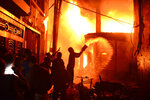In this Wednesday, Feb. 20, 2019, photo, firefighters and local people help douse a fire in Dhaka, Bangladesh. A devastating fire raced through at least five buildings in an old part of Bangladesh's capital and killed scores of people. (AP Photo/Mahmud Hossain Opu)