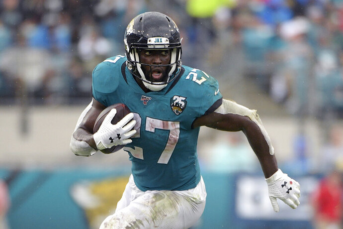 """FILE - In this Oct. 27, 2019, file photo, Jacksonville Jaguars running back Leonard Fournette (27) rushes for yardage against the New York Jets during the first half of an NFL football game, in Jacksonville, Fla. Fournette had a series of meetings and calls this week after carrying the ball a season-low eight times in a 20-point loss to Indianapolis. The most notable of them was chatting with 1981 Heisman Trophy winner and retired Oakland Raiders star Marcus Allen, who told the third-year pro about his experience having to play fullback and share a backfield with fellow Heisman winner Bo Jackson more than 30 years ago. """"His situation was harder than mine,"""" said Fournette, who first met Allen during a recruiting visit to USC while he was in high school.(AP Photo/Phelan M. Ebenhack, File)"""
