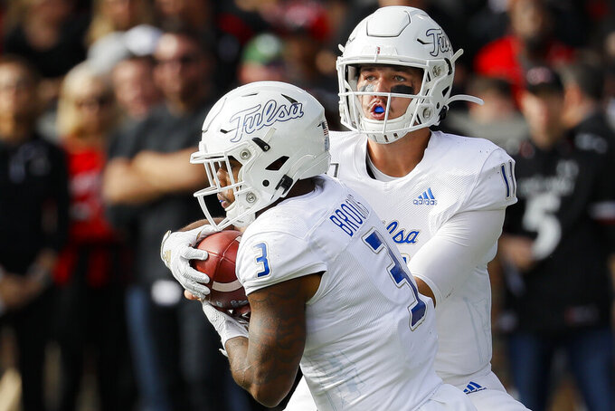 Tulsa running back Shamari Brooks (3) receives the ball from quarterback Zach Smith (11) during the first half of an NCAA college football game against Cincinnati, Saturday, Oct. 19, 2019, in Cincinnati. (AP Photo/John Minchillo)