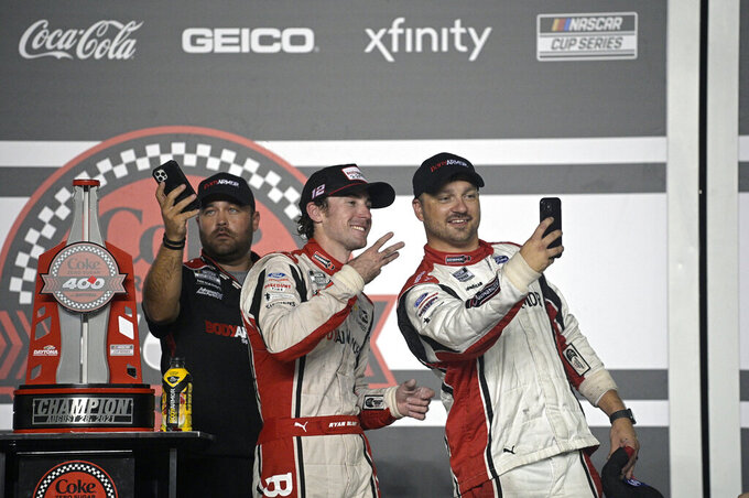 Ryan Blaney, center, poses with the champion trophy and crew members in Victory Lane after winning a NASCAR Cup Series auto race at Daytona International Speedway, Saturday, Aug. 28, 2021, in Daytona Beach, Fla. (AP Photo/Phelan M. Ebenhack)
