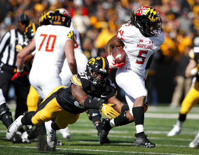 FILE - In this Saturday, Oct. 20, 2018, file photo, Maryland running back Anthony McFarland (5) is tackled by Iowa defensive end Chauncey Golston (57) during the second half of an NCAA college football game, in Iowa City, Iowa. McFarland started only five games as a freshman, yet still managed to top the 1,000-yard mark. He raised eyebrows around the Big Ten after running for 298 yards against Ohio State. Now he's poised to become one of the league's dominant backs. (AP Photo/Charlie Neibergall, File)