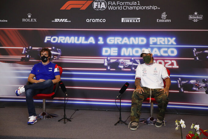 Alpine driver Fernando Alonso of Spain, left, sits by Mercedes driver Lewis Hamilton of Britain during a press conference ahead of Sunday's Formula One race, in Monaco, Wednesday, May 19, 2021. (Sebastian Nogier, Pool via AP)