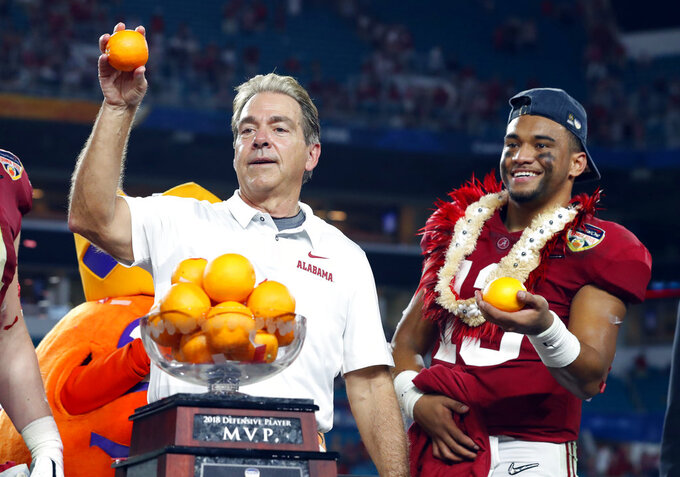 Alabama head coach Nick Saban and quarterback Tua Tagovailoa, throw oranges to the team during the Orange Bowl NCAA college football game trophy presentation, Sunday, Dec. 30, 2018, in Miami Gardens, Fla. Alabama defeated Oklahoma 45-34. (AP Photo/Wilfredo Lee)