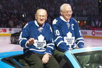 FILE - In this Feb. 16, 2013, file photo, former Toronto Maple Leafs players George Armstrong, right, and Johnny Bower are paraded around the ice at the 50th anniversary of the team's 1963 Stanley Cup victory ahead of a Maple Leafs game against the Ottawa Senators in Toronto. Armstrong, who captained the Maple Leafs to four Stanley Cups in the 60s and wore the blue and white his entire career, has died. He was 90. The Maple Leafs confirmed the death Sunday, Jan. 24, 2021, on Twitter. (Chris Young/The Canadian Press via AP, File)