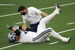 Dallas Cowboys guard Zack Martin (70) is assisted by team medical staff after suffering an unknown injury in the first half of an NFL football game against the Washington Football Team in Arlington, Texas, Thursday, Nov. 26, 2020. (AP Photo/Roger Steinman)