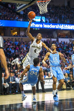 Wake Forest's Torry Johnson (4) goes to the basket as North Carolina's Kenny Williams defends (4) during the first half of an NCAA college basketball game in Winston-Salem, N.C., Saturday, Feb 16, 2019. (AP Photo/Woody Marshall)