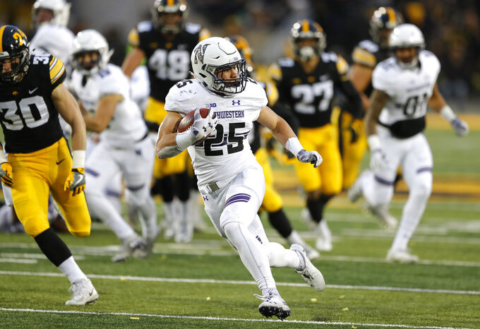 Northwestern running back Isaiah Bowser runs up field during a 34-yard touchdown run in the second half of an NCAA college football game against Iowa, Saturday, Nov. 10, 2018, in Iowa City, Iowa. Northwestern won 14-10. (AP Photo/Charlie Neibergall)