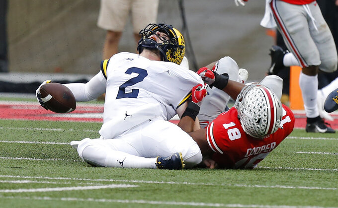 Ohio State defensive end Jonathon Cooper, right, sacks Michigan quarterback Shea Patterson during the first half of an NCAA college football game Saturday, Nov. 24, 2018, in Columbus, Ohio. (AP Photo/Jay LaPrete)