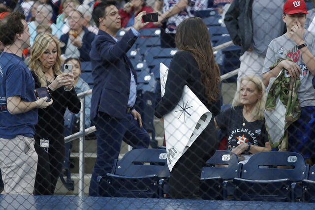 A ballpark official takes a sign from a fan before spring training baseball game between the Houston Astros and Washington Nationals Saturday, Feb. 22, 2020, in West Palm Beach, Fla. (AP Photo/John Bazemore)