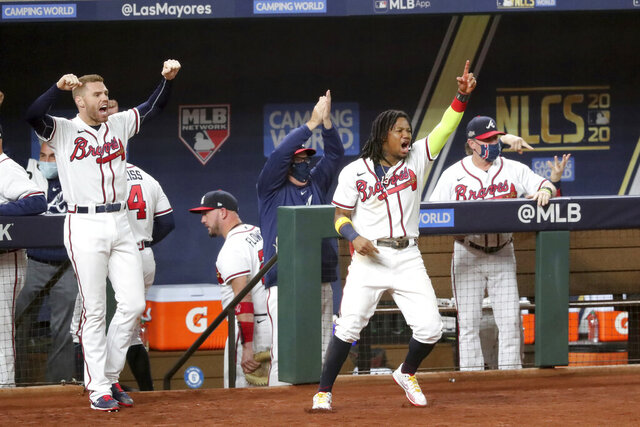 Atlanta Braves first baseman Freddie Freeman, front left, right fielder Ronald Acuna, front right, and teammates react in the dugout after shortstop Dansby Swanson (not shown) hit a two-run double against the Los Angeles Dodgers during the sixth inning in Game 4 Thursday, Oct. 15, 2020, for the best-of-seven National League Championship Series in Arlington, Texas. (Curtis Compton/Atlanta Journal-Constitution via AP)