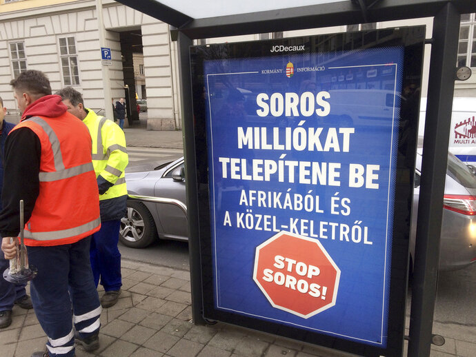 "In this photo taken Feb. 1, 2018 a poster is photographed in Budapest reading: Soros would settle millions from Africa and the Middle East. Stop Soros!. The Hungarian government said Tuesday Feb. 13, 2018 that it is sending a draft bill dubbed ""Stop Soros"" to parliament. The bill targets non-governmental organizations which it says are working to bring migrants to Hungary. (AP Photo/Pablo Gorondi)"