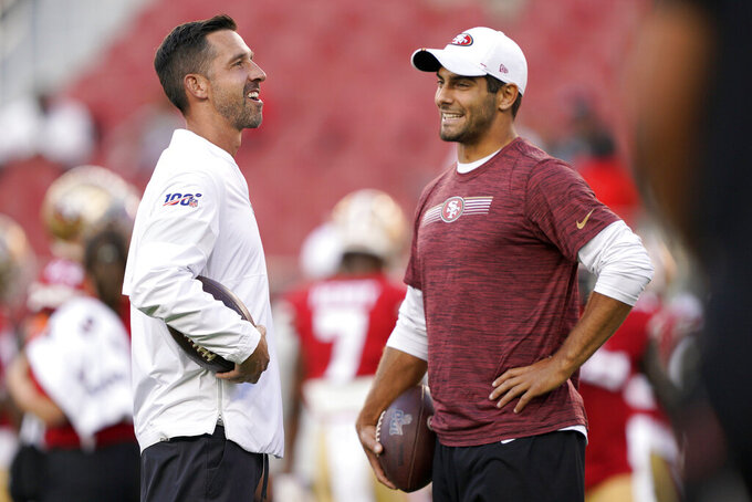 San Francisco 49ers coach Kyle Shanahan, left, talks with quarterback Jimmy Garoppolo before the team's NFL preseason football game against the Los Angeles Chargers in Santa Clara, Calif., Thursday, Aug. 29, 2019. (AP Photo/Tony Avelar)