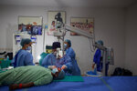 "Nepal's ""God of Sight"", Dr. Sanduk Ruit performs a simple surgical technique to remove cataracts at an eye camp in Lumbini, 288 kilometers (180 miles) south west of Kathmandu, Nepal, March 31, 2021. The eye doctor renowned for his innovative and inexpensive cataract surgery for the poor is taking his work beyond the Himalayan mountains to other parts of the world so there is no more unnecessary blindness in the world. Ruit, who has won many awards for his work and performed some 130,000 cataract surgery in the past three decades, is aiming to expand his work beyond the borders of his home country and the region to go globally. (AP Photo/Bikram Rai)"