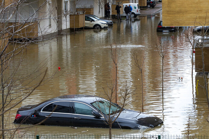 Stranded residents try to reach their cars in the flooded street, following heavy rain and snowfall in Fushe Kosove, Kosovo on Monday, Jan. 11, 2021. Many roads have been blocked and bridges damaged, according to the authorities. There have been no casualties or lost livestock so far. (AP Photo/Visar Kryeziu)