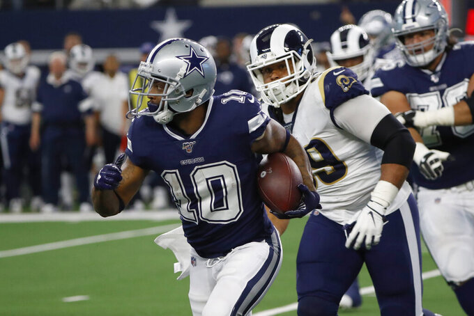 Dallas Cowboys wide receiver Tavon Austin (10) carries the ball past Los Angeles Rams defensive tackle Aaron Donald, front right, in the first half of an NFL football game in Arlington, Texas, Sunday, Dec. 15, 2019. (AP Photo/Roger Steinman)
