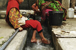 "In this Monday, July 9, 2018, photo, Ansa Khan cools her feet with running water just adjacent to her home while her mother and sister are busy in their household activities and washing clothes and utensils in Mardan, Pakistan. Since 2012 the United Nations has reserved Oct. 11 as the International day of the Girl Child ""to recognize girls' rights and the unique challenges girls face around the world."" This year the theme is employable skills for girls, particularly in the poorer economies. (AP Photo/Saba Rehman)"