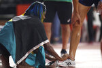 Shaunae Miller-Uibo, of Bahamas, who took silver in the women's 400m unties the shoes of her husband Maicel Uibo, of Estonia, who took silver in the men's decathlon at the World Athletics Championships in Doha, Qatar, Friday, Oct. 4, 2019. (AP Photo/Petr David Josek)