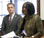 As Gov. Ralph Northam, left, looks on, Chief Deputy Attorney General Cynthia Hudson, left, addresses a gathering as she presented the report from The Commission to Examine Racial Inequity in Virginia Law in Richmond, Va., Thursday, Dec. 5, 2019. (Bob Brown/Richmond Times-Dispatch via AP)