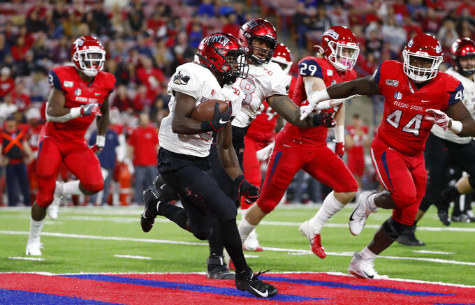 UNLV running back Charles Williams tries to get around Fresno State defensive lineman Leevel Tatum III, right, during the first half of an NCAA college football game in Fresno, Calif., Friday, Oct. 18, 2019. (AP Photo/Gary Kazanjian)